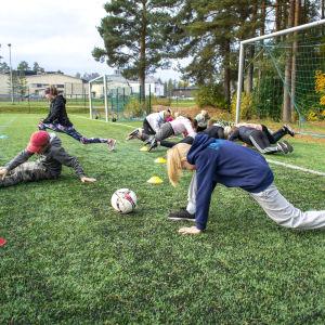 Oppilaat venyttelevät urheilukentällä.