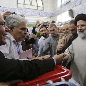 Presidentkandidaten Ebrahim Raisi (i svart turban) hälsar på valfunktionärer i en vallokal i Teheran. 19.5.2017