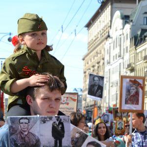 Många barn kläs i uniform under segerdagsfirandet. En liten uniformklädd pojke sitter på en mans axlar.