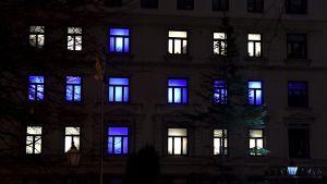 Ett höghus i Helsingfors firar självständighetsdagen med belysning i vitt och blått.