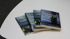 Fyra böcker skrivna av Mathias Rosenlund på ett vitt bord.