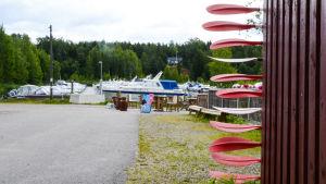 Bakom ett rött skjul till höger sticker en massa paddlar ut. Längre fram syns stranden med flera båtar.