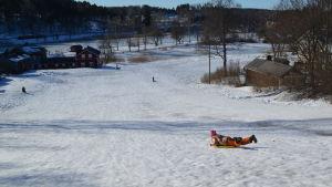 Barn som glider ner för borgbacken i borgå med pulka