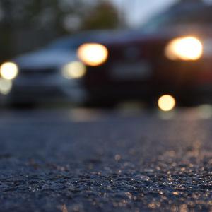 Mörker, asfalt och ljus från billyktor.
