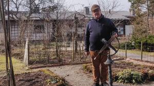 En man står vid ett solur i en trädgård.