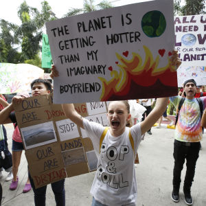 "En klimatdemonstrant håller upp ett plakat med texten ""The climate is getting hotter than my imaginary boyfriend""."