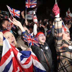 En folkmassa jublar och viftar med Storbritanniens flaggor, tre glada damer i förgrunden med händerna i luften.