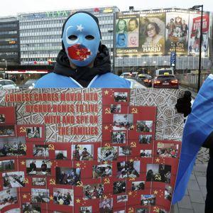 En man med blå mask som håller i ett plakat.