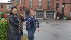 Lotta Lerviks och Karin Svahnström står vid en grön häck. I bakgrunden syns en större byggnad av tegel.