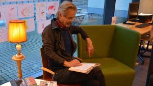 Pentti Vähätalo läser högt för vuxna på biblioteket i Kimito.