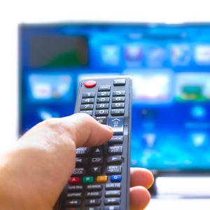 En hand håller i en fjärrkontroll och riktar den mot tv:n.