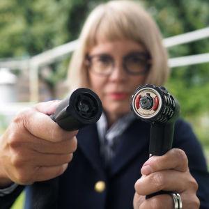 Kvinna med glasögon håller upp uppsågat cykellås mot kameran. Det är ett kombinationslås.