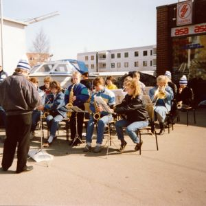 Hannu Sopanen johtaa nuorista soittajista koostuvaa jazzorkesteria Vuoksenniskan torilla, Jouni Järvelä soittaa seisten sooloa.