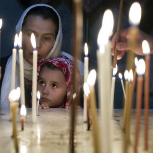 A child with her mother light candles in a chapel in the Church of the Holy Sepulchre in Jerusalem's Old City on Easter Sunday, 20 April 2014. The church is the accepted site of Jesus Christ's crucifixion, burial and resurrection.