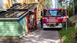 Brandbil och brandmän vid ytterdörren där en soffa tog eld