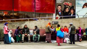 Drygt tio kvinnor och män sitter på parkbänkar och står intill utanför Kulturhuset i Stockholm.