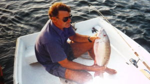 Bild på Seppo Sarekoski i en glasfiberbåt. Han har fått napp, en stor fisk i famnen.