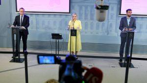 Mika Lintilä, Maria Ohisalo och Timo Harakka står vid talarpodium och håller presskonferens.