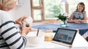 Nainen leipoo eli kaataa jauhoja kulhoon katsoen reseptiä tablettitietokoneelta.