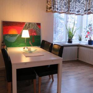 ett rum med matbord, stolar och en färggrann tavla som står på bordet och lutar mot väggen. Ett fönster med pålistrade dekaler (fjärilar och blommor)