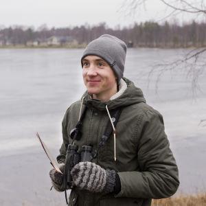 Akseli Myllyneva, joka on vuoden 2020 nuori lintuharrastaja pitelee kuvassa kiikareita ja hymyilee.