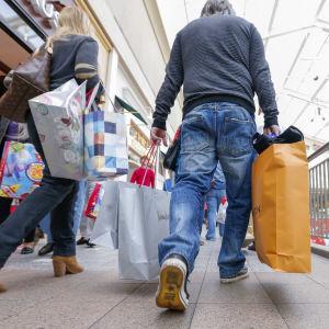 Två personer som håller i shoppingkassar under Black Friday.