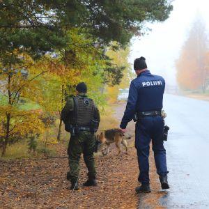 Två poliser står med ryggen vänd mot en kamera, en polishund går framför poliserna.