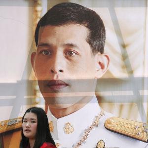 En student passerar förbi kungens porträtt i Bangkok