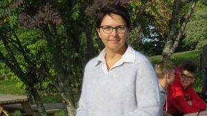 En kvinna med brunt hår och glasögon på en gård, där det finns skolelever i bakgrunden, men man ser dem inte så bra.