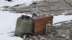 Stormlyktor och vattenkanister som behövs för övernattning i skogen.