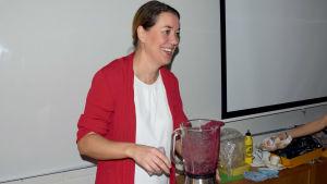 En kvinna i röd tröja och vit skjorta fixar smoothie med hjälp av en mixer/maskin för smoothies. Hon är i ett klassrum och ser glad ut.