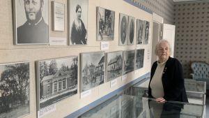 En äldre kvinna står i ett musem vid en vägg fullt av gamla fotografier.