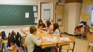 barn äter lussekatter i klassrum