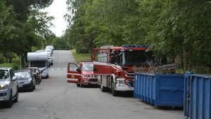 Två av räddningsverkets fordon på en liten asfalterad väg.