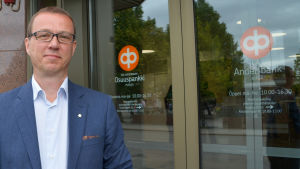 Mauri Molander, vd för Östnylands andelsbank framför bankens dörr i Borgå