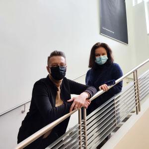 En man och en kvinna i munskydd står i en trappa.