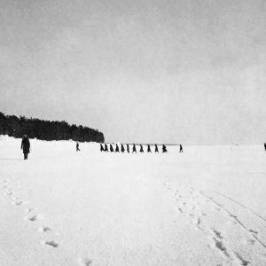 Svartvitt foto från 1921. Svarta skepnader på havsisen nära stranden. De första flyktingarna kommer.
