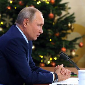 Vladimir Putin sitter vid sitt bord i sidoprofil och har en dekorerad julgran i bakgrunde. Putin har knäppt sina händer.