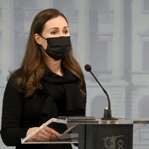 Sanna Marin på presskonferensen framför podiet i svart klänning och utsläppt hår.