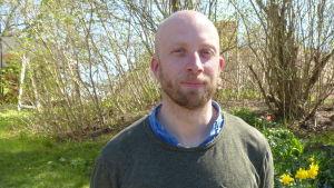 Carl Sebastian Lindberg utomhus. Grön gräsmatta, lite tulpaner, påskliljor och blå himmel i bakgrunden