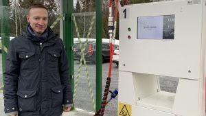 En man står intill ett tankställe för biogas