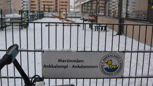 """En skylt med texten """"Martinmäen Ankkalampi - Ankdammen"""" på ett staket till ett daghem."""