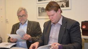 Två tjänstemän i Raseborg sitter, båda i kavaj och skjorta. Den ena tittar på sina papper och den andra håller pappren i handen och tittar i kameran. Till vänster Mårten Johansson och till höger Jan Gröndahl.