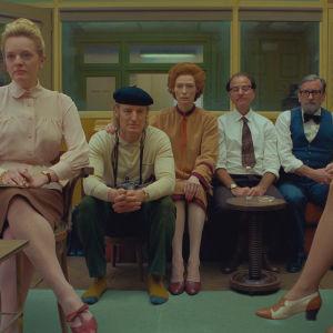 Allvarliga miner på redaktionen, sittande på rad Alumni (Elisabeth Moss), Herbsaint Sazerac (Owen Wilson), J.K.L. Berensen (Tilda Swinton) och två andra som jobbar på redaktionen, skådespelarna Fisher Stevens och Griffin Dunne.