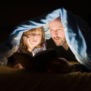 Isä ja poika peiton alla lukemassa kirjaa