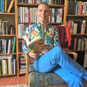 Jari Järvelä istuu tuolissa kirjahyllyn edessä kirja kädessä