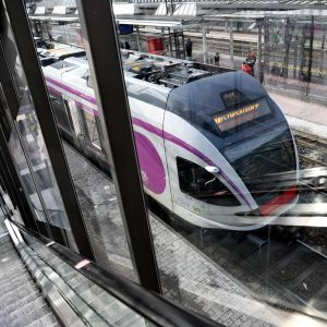 Ett vitt tåg med lila detaljer vid en perrong