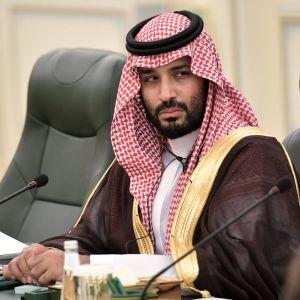 Kruununprinssi istuu pöydän takana perinteisessä asussa.