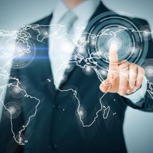 Futuristisk bildsättningsbild där en man petar på en världskarta med olika delar kopplade till varandra genom nätverk.