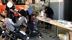 Personer och barnvagnar vid ett bord med nallar i bakgrunden.